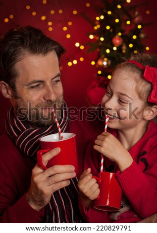 Christmas eve - happy family time. Smiling father and daughter drink cocoa and having fun on dark red background with lights. - stock photo