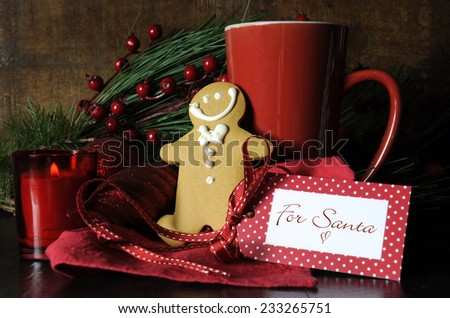 Christmas Eve setting with gingerbread and red cup of coffee for Santa in traditional dark wood rustic setting. - stock photo