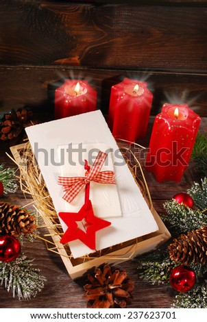 christmas eve wafers lying  on hay and red candles on wooden table