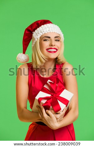 Christmas excitement. Happy young woman in santa's hat cuddle a gift. Waist up studio shot isolated on green. - stock photo