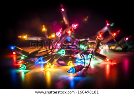 Christmas fairy lights isolated on reflecting surface. - stock photo