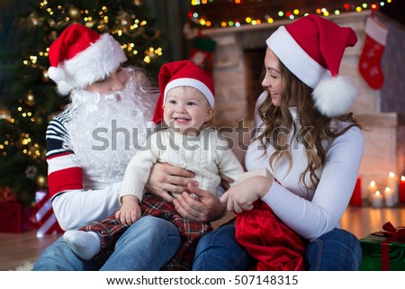 Christmas family - baby and his mom and daddy in festive living room