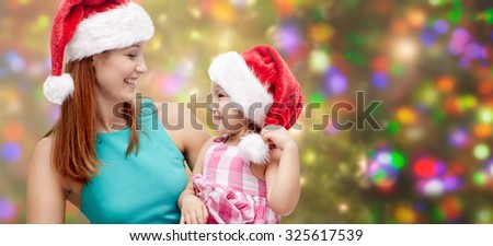 christmas, family, childhood and people concept - happy mother and little girl in santa hats over holidays lights background - stock photo