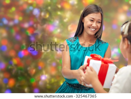 christmas, family, childhood and people concept - happy mother giving present to her daughter rover holidays lights background - stock photo