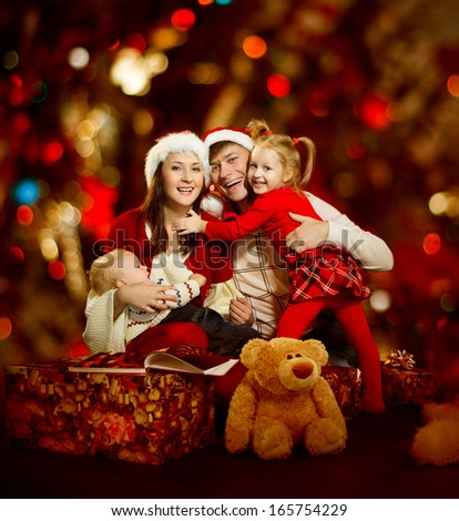 Christmas family of four persons happy smiling over red background - stock photo