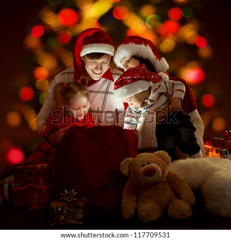 Christmas family of four persons in red hats opening lighting bag with gifts