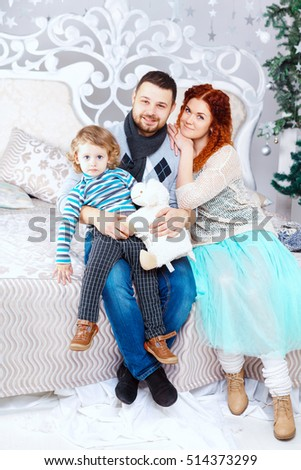 Christmas family of three persons mother father and son two year old boy and fir tree with gift boxes over white bedroom background