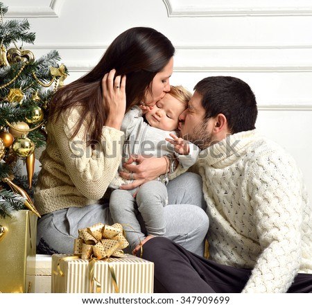 Christmas Family with baby Kid and gold present gifts. Happy kissing Parents and Child at Home Celebrating New Year. Christmas Tree. Christmas scene - stock photo