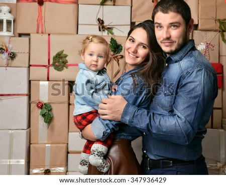 Christmas Family with baby toddler Kid on rustic craft presents gift wall. Happy Parents and Child at Home Celebrating New Year. Christmas scene - stock photo