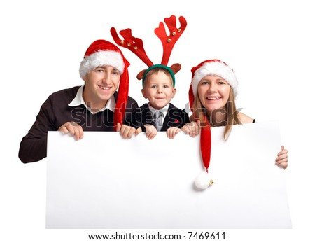 Christmas family with banner. Happy family of three in Christmas hats holds white banner - stock photo