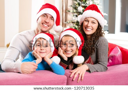 Christmas Family with Kids. Happy Smiling Parents and Children at home. Christmas Tree. Santa Hat.Father,mother,sister and brother Celebrating New Year together - stock photo