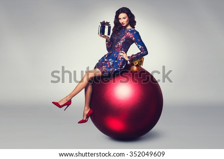 Christmas fashion photo of a nice woman sitting on a big red bauble holding a christmas gift - stock photo