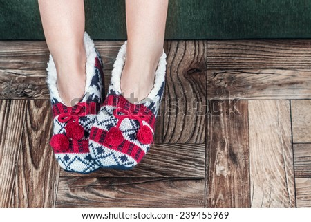 Christmas female legs in slippers on the background of the parquet floor - stock photo