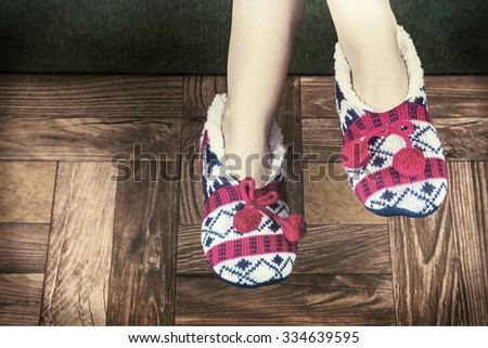 Christmas female legs in slippers on the background of the parquet floor. toned image - stock photo