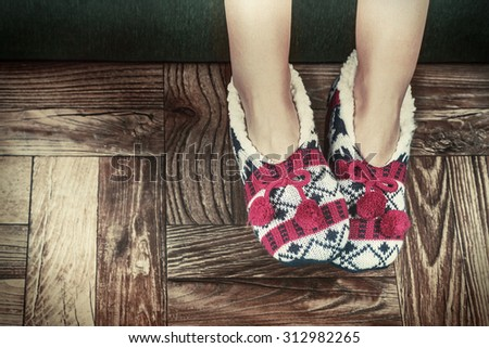 Christmas female legs in slippers on the background of the parquet floor. toning image - stock photo