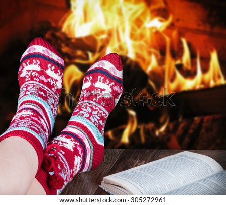 Christmas female legs in socks on the background of a burning fireplace - stock photo