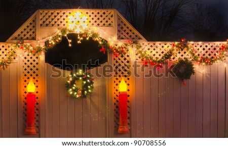 Christmas fence with garland, lights, wreaths and candles. - stock photo