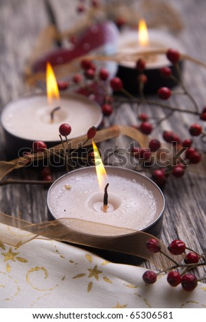 Christmas festive candles with Christmas balls and dog rose hips - stock photo