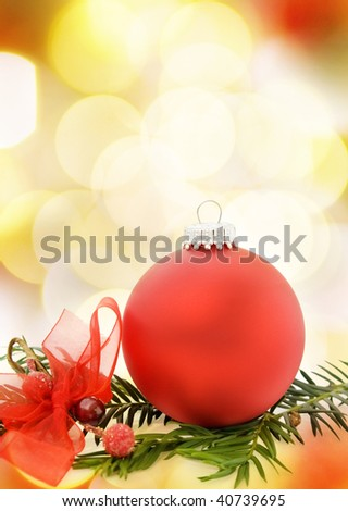 Christmas festive card with red bauble over defocused lights.