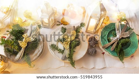 Christmas festive table setting decoration with tableware,fir tree branches, ribbon, lantern with candles