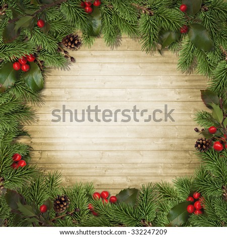 Christmas fir branches and holly on wooden board