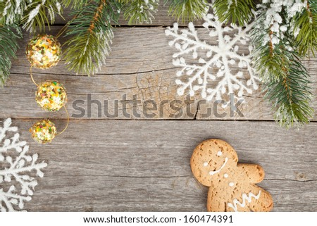 Christmas fir tree and decor covered with snow on wooden board background - stock photo