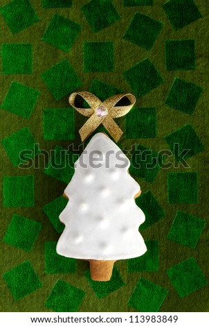 Christmas fir tree background. Ginger and Honey cookie with white sugar decoration and gold bow on the green paper background. - stock photo