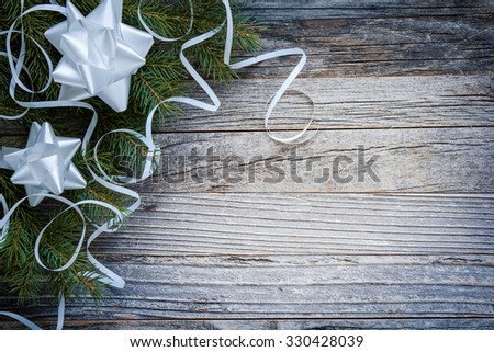Christmas fir tree branch with white decorations on an old wooden background, top view. Copy space for text.