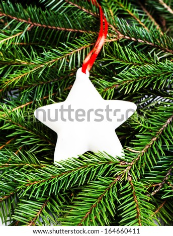 Christmas Fir Tree Branches and Christmas decoration with white Star and Red Ribbon may use as background. Christmas Card. - stock photo