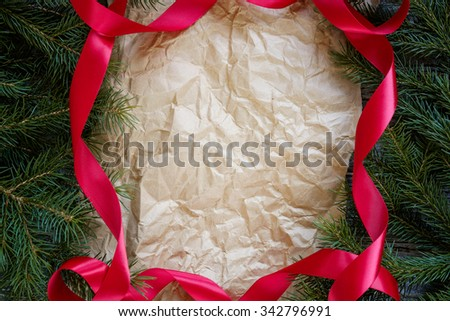 Christmas fir tree branches and red ribbon frame an old paper, copy space for text, top view.