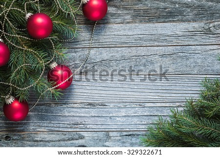 Christmas fir tree branches with decorations on an old wooden background, copy space for text, top view.