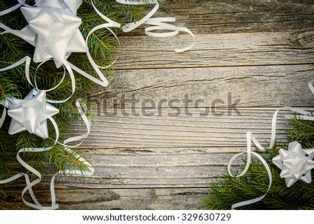 Christmas fir tree branches with white decorations on a rustic wooden plank, copy space for text, top view.