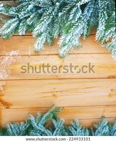 Christmas fir tree covered with snow on wooden  background - stock photo