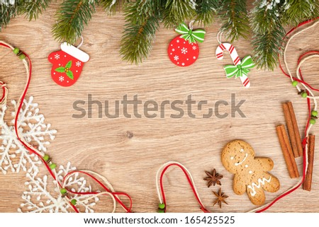 Christmas fir tree, gingerbread cookie and decor on wooden background - stock photo