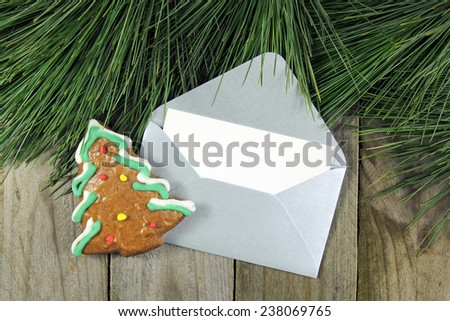christmas fir tree, silver envelope with gingerbread on wooden b - stock photo