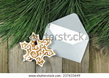 christmas fir tree, silver envelope with gingerbread on wooden background - stock photo