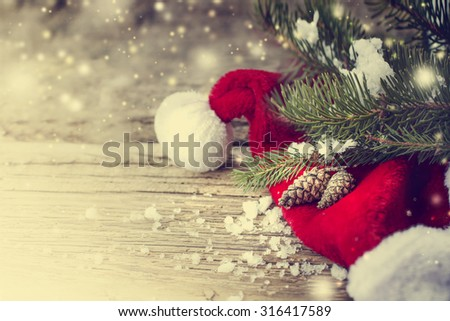 Christmas fir tree with cones,christmas red hat and snow on a wooden background/ Christmas background - stock photo