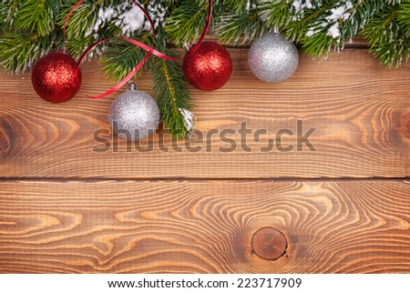 Christmas fir tree with snow and baubles on rustic wooden board with copy space - stock photo