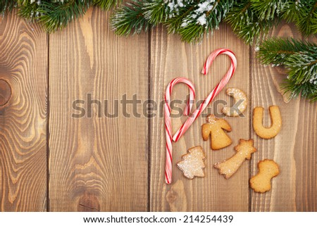 Christmas fir tree with snow, candy cane and gingerbread cookies on rustic wooden board with copy space - stock photo