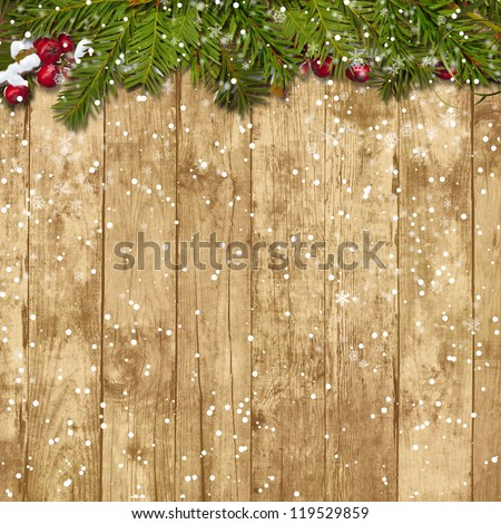 Christmas fir twig with red berries on the wooden background - stock photo