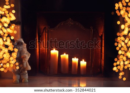 Christmas fireplace with burning candles and lights bokeh in home interior - stock photo