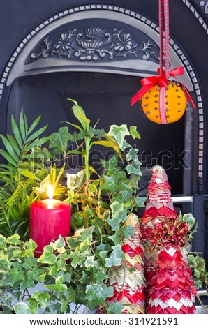 Christmas Fireside Decoration A christmas fire side display with a Christingle decoration - stock photo