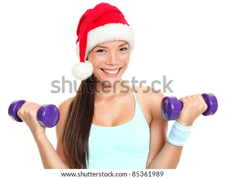 Christmas fitness sport woman wearing santa hat doing gym exercise training arms lifting dumbbells. Mixed race Chinese Asian Caucasian female fitness model isolated on white background. - stock photo