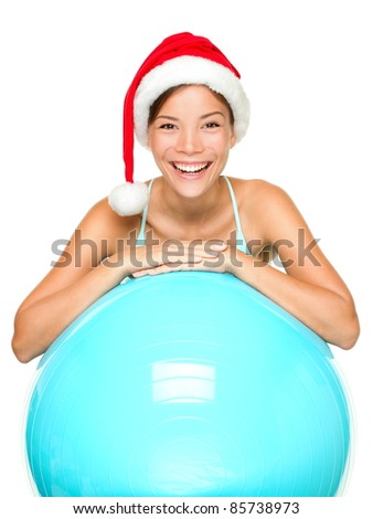 Christmas fitness woman on exercise ball wearing santa hat smiling joyful and happy. Beautiful cheerful mixed race Asian Caucasian female fitness model isolated on white background. - stock photo