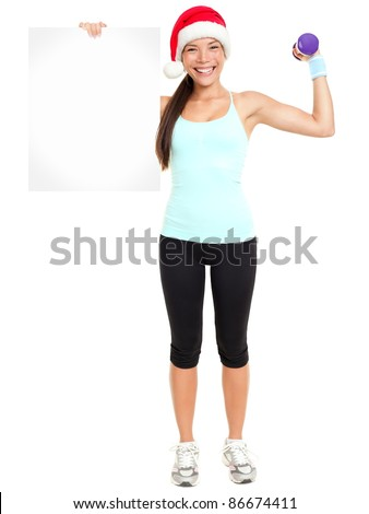 Christmas Fitness woman showing sign billboard wearing christmas Santa hat. Full length portrait isolated on white background.