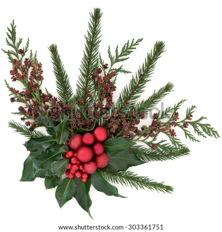Christmas flora with red baubles, holly, ivy, fir and winter greenery over white background. - stock photo