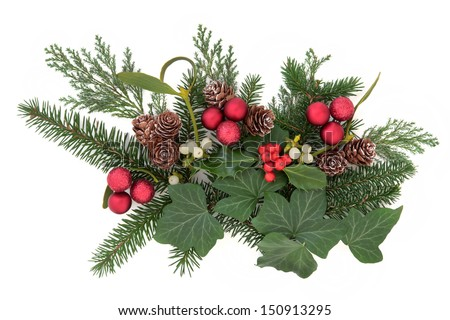 Christmas floral arrangement with red baubles, holly, ivy, mistletoe, pine cones and winter greenery over white background. - stock photo