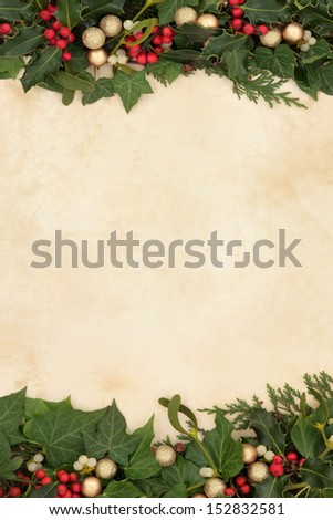 Christmas floral background border with gold baubles, holly, ivy and mistletoe on old parchment paper. - stock photo