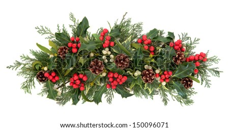 Christmas floral decoration with holly, ivy, mistletoe, pine cones and winter greenery over white background. - stock photo