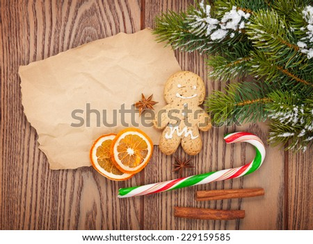 Christmas food and decor with snow fir tree over wooden table with paper for copy space - stock photo